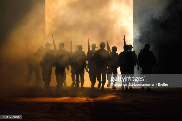 rear view of silhouette special forces soldiers walking with guns and smoke over light background - army stock pictures, royalty-free photos & images