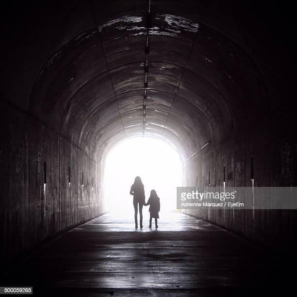 rear view of silhouette woman and girl holding hands in subway - daughters of darkness stock pictures, royalty-free photos & images