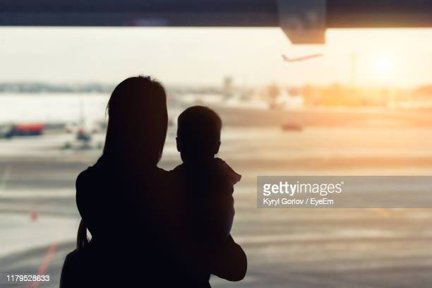 rear view of silhouette woman holding with baby boy at airport - toddler at airport stock pictures, royalty-free photos & images