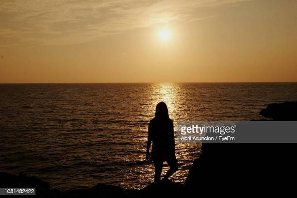 Rear View Of Silhouette Woman Looking At Sea During Sunset
