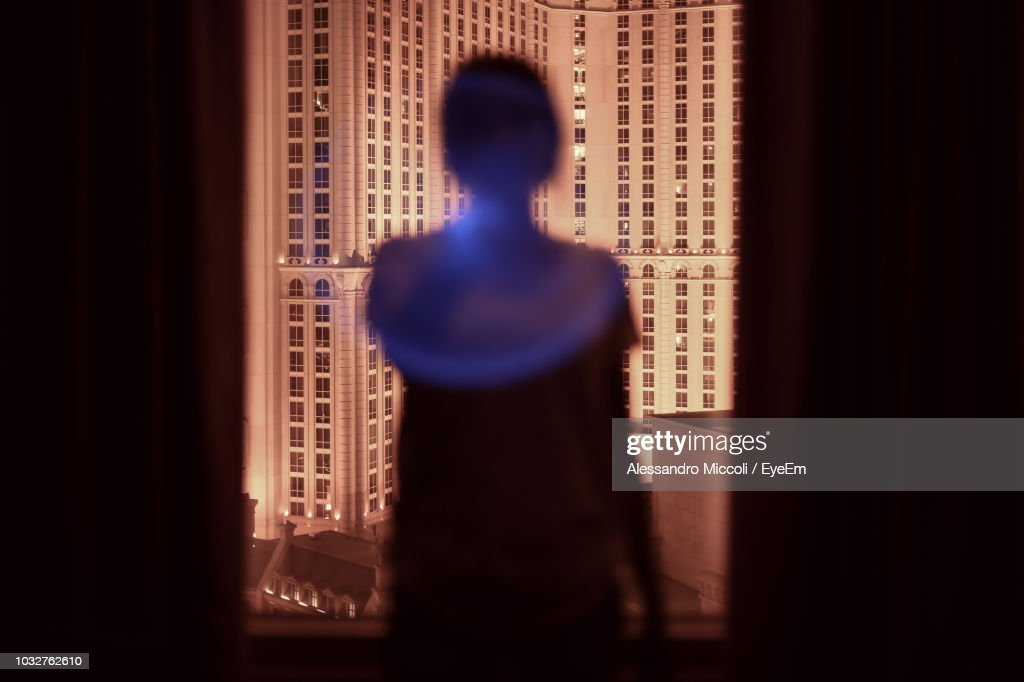 Rear View Of Silhouette Woman Looking Through Window While Standing In Darkroom : Foto de stock