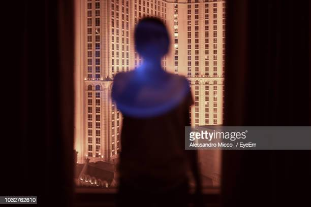 rear view of silhouette woman looking through window while standing in darkroom - alessandro miccoli stockfoto's en -beelden