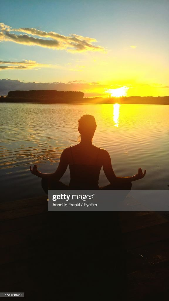 Rear View Of Silhouette Woman Meditating At Beach Against Sky During Sunset : Photo
