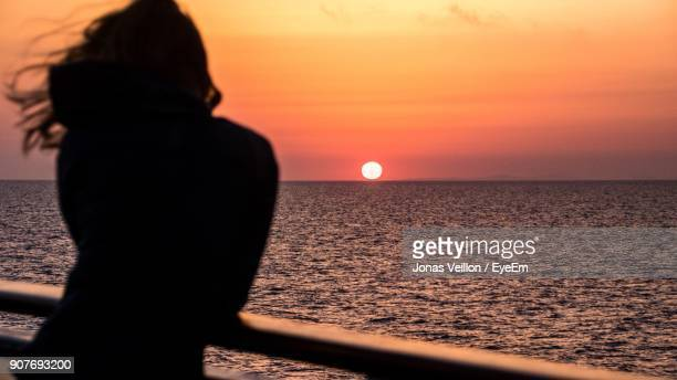 Rear View Of Silhouette Woman Standing By Railing At Beach During Sunset
