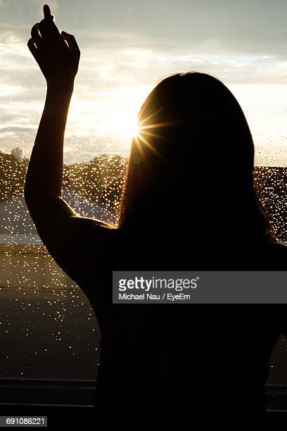 Rear View Of Silhouette Woman Standing By Wet Glass Window During Sunset
