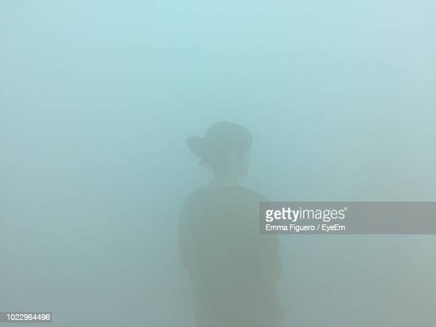 rear view of silhouette woman standing during foggy weather - nebel stock-fotos und bilder