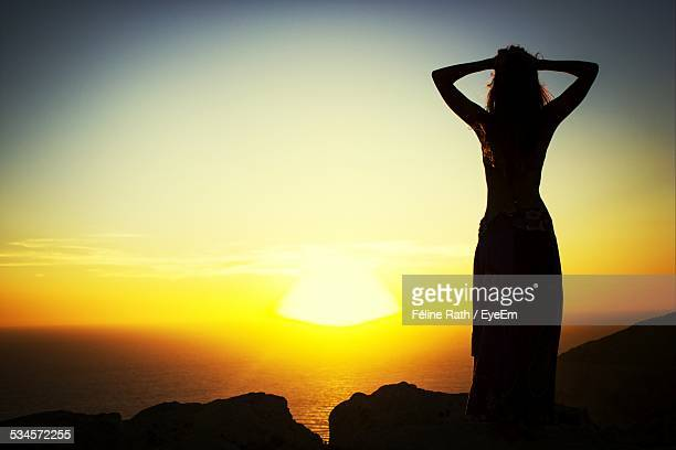 Rear View Of Silhouette Woman Standing On Hill In Front Of Sea During Sunset