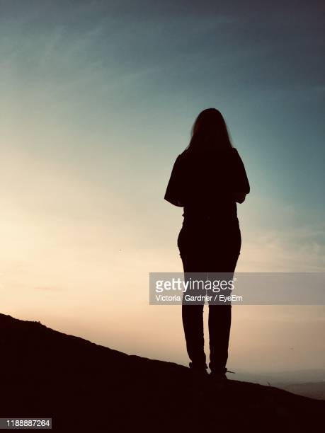 rear view of silhouette woman standing on land against sky during sunset - in silhouette stock pictures, royalty-free photos & images