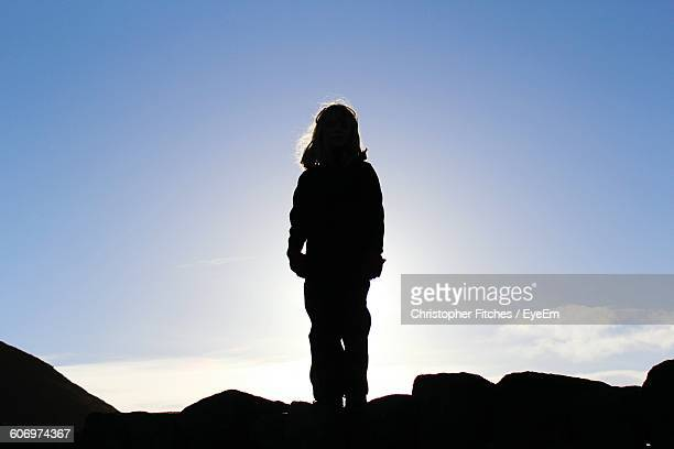 Rear View Of Silhouette Woman Standing On Rock Against Sky