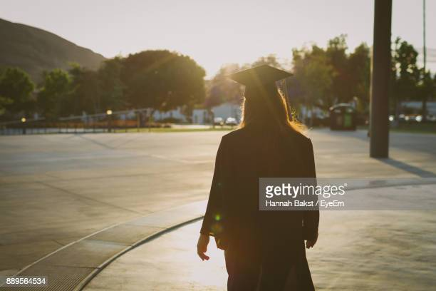 Rear View Of Silhouette Woman Walking On Street Against Sky During Sunset