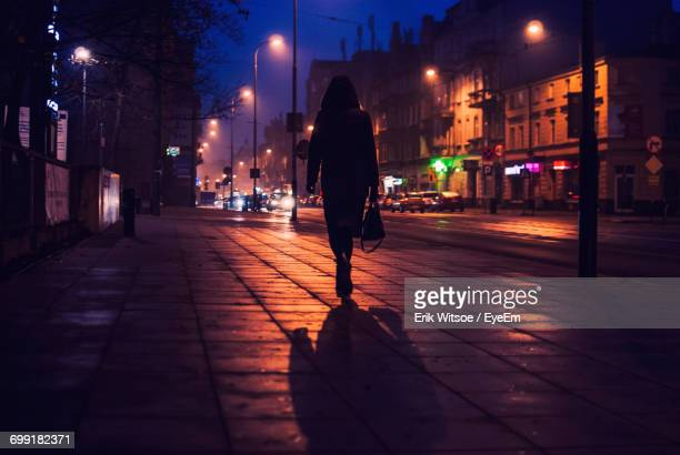 Rear View Of Silhouette Woman Walking On Street In City At Night