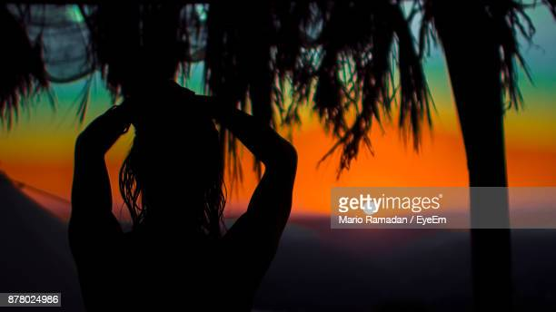 Rear View Of Silhouette Woman With Arms Raised Standing Against Sky During Sunset