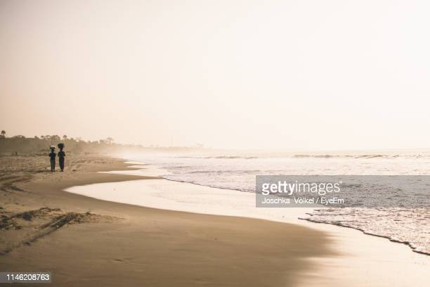 rear view of silhouette women walking at beach against clear sky during sunset - gambia stock photos and pictures