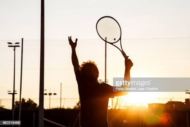 rear view of silhouette young man playing tennis at court - テニス ストックフォトと画像