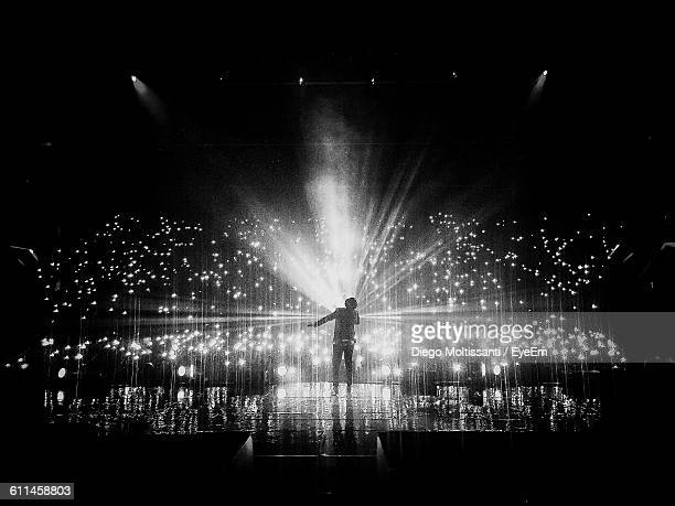 rear view of singer performing on stage at music concert - stage light stock pictures, royalty-free photos & images