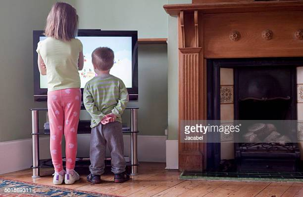 Rear view of sister and brother standing too close to and watching TV