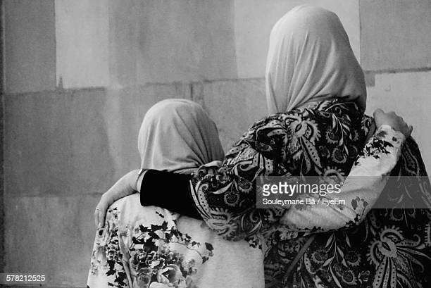 Rear View Of Sisters In Hijab With Arms Around