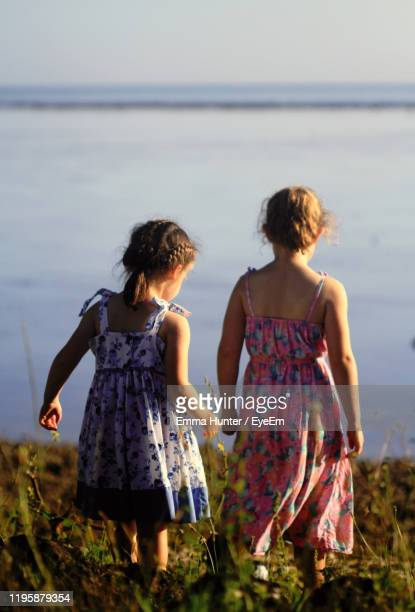rear view of sisters looking at sea while standing on land - emma hunter eye em stock photos and pictures