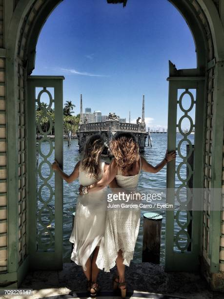 Rear View Of Sisters Standing On Archway At Villa Vizcaya