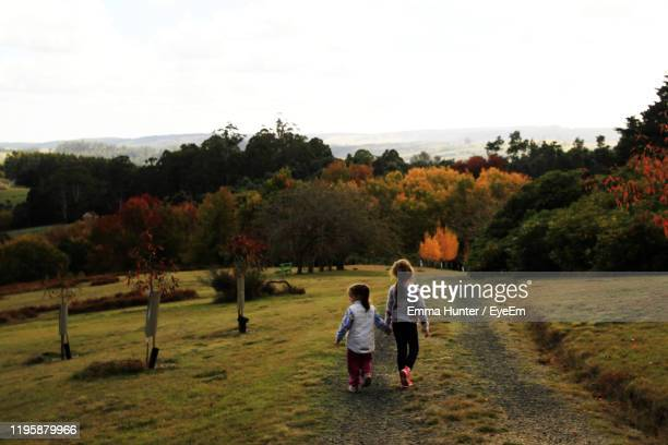 rear view of sisters walking on grassy land against clear sky - emma hunter eye em stock photos and pictures