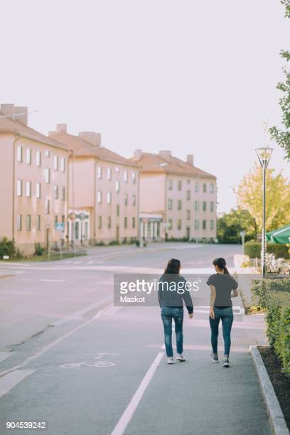 Rear view of sisters walking on street in city against clear sky