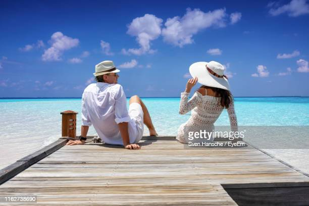 rear view of sitting on wooden jetty at beach against sky - jetty stock pictures, royalty-free photos & images