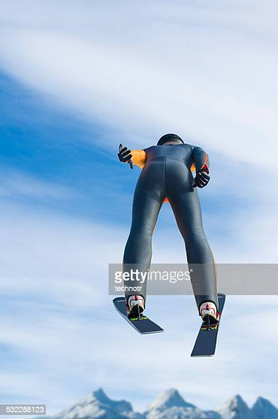 rear view of ski jumper flying against the blue sky - ski jumping stock pictures, royalty-free photos & images