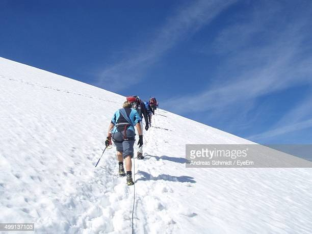 Rear view of skiers climbing snowy mountain