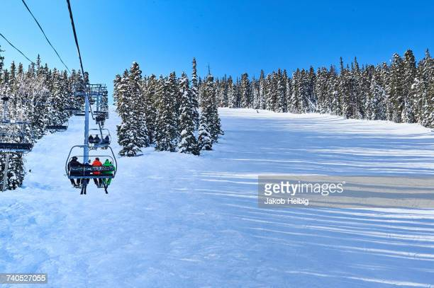 Rear view of skiers on ski lift moving up snow covered landscape, Aspen, Colorado, USA