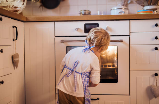 a rear view of small boy looking in the oven indoors, baking. - 焗 預備食物 個照片及圖片檔