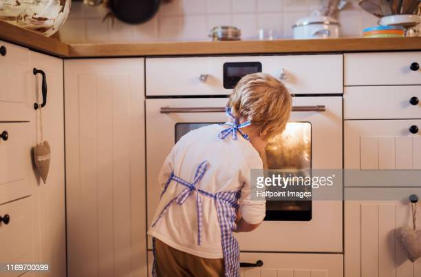 a rear view of small boy looking in the oven indoors, baking. - 焼いた ストックフォトと画像