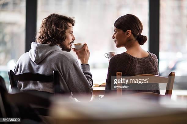 の後ろからの眺め笑顔のカップルのお気に入りのカフェをお楽しみいただけます。