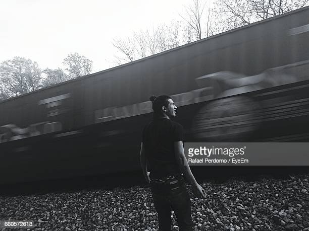 Rear View Of Smiling Man Looking At Blur Train Against Clear Sky
