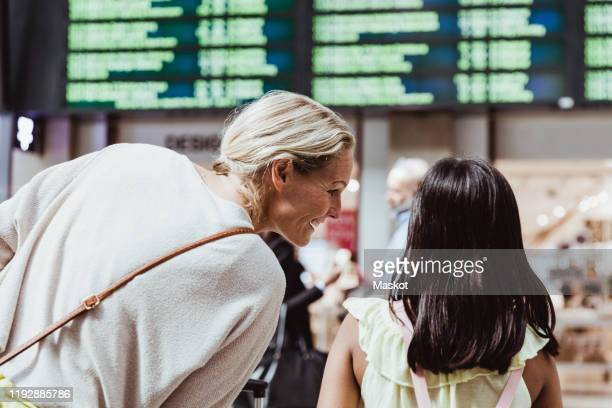 rear view of smiling mother talking to daughter at railroad station - railway station stock pictures, royalty-free photos & images