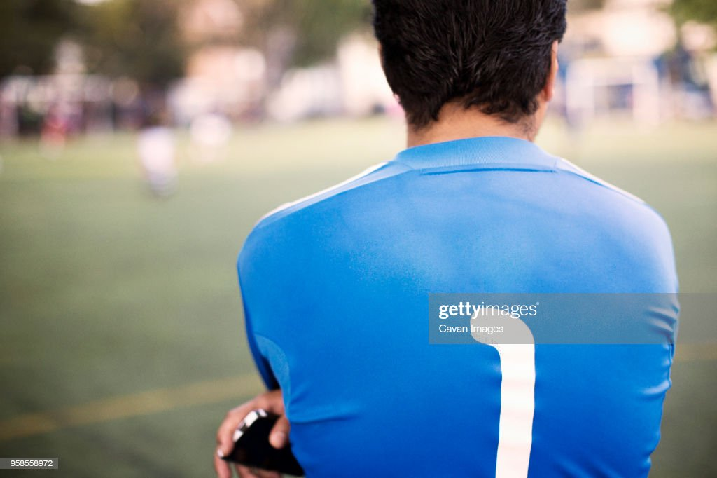 Rear view of soccer player standing at field : Stock Photo