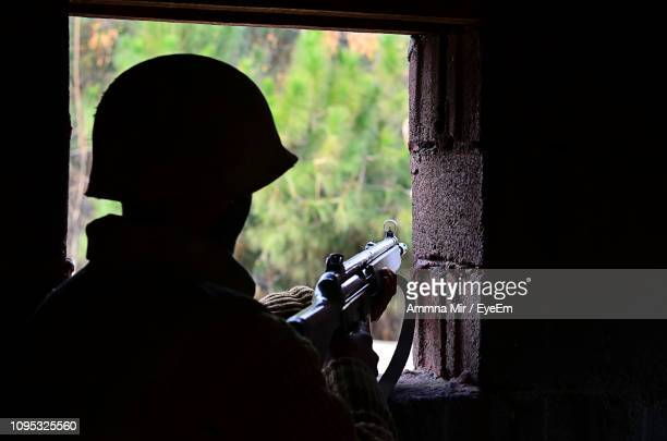 rear view of soldier holding rifle - terrorism stock pictures, royalty-free photos & images