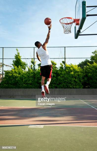 rear view of sportsman dunking ball in hoop at court - バスケットボールのシュート ストックフォトと画像