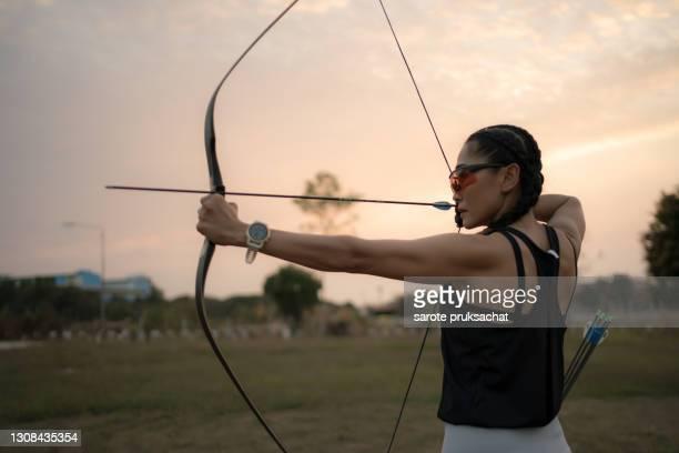 rear view of sportswoman doing archery on a sports field against sunset . - tirare la palla foto e immagini stock