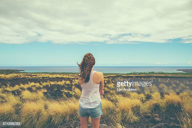 rear view of standing woman looking prairie field - canadian prairies stock photos and pictures