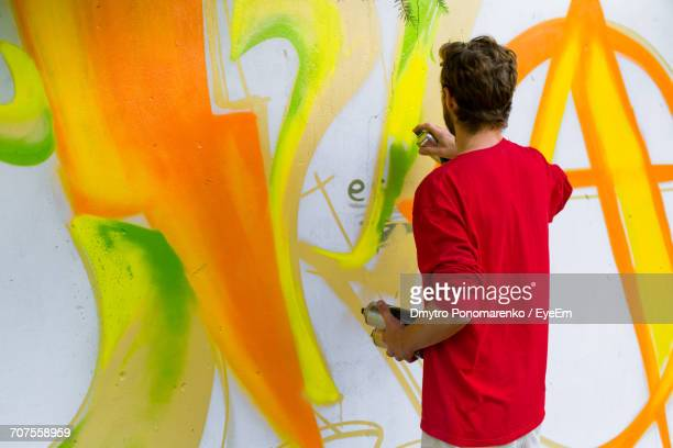 rear view of street artist painting graffiti on wall - street artist stock photos and pictures