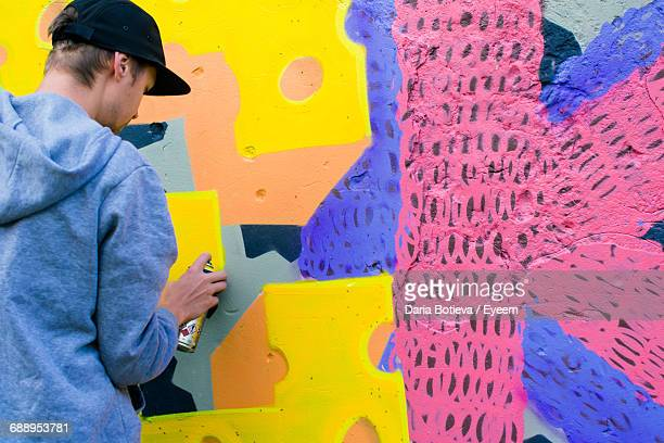 rear view of street artist painting wall with spray paint - street artist stock photos and pictures
