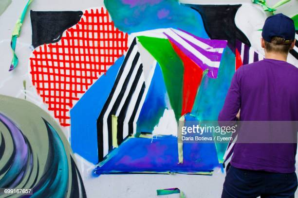 rear view of street artist standing by colorful graffiti on wall - street artist stock pictures, royalty-free photos & images