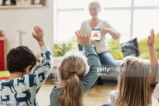 Rear view of students raising hands while teacher showing digital tablet at preschool