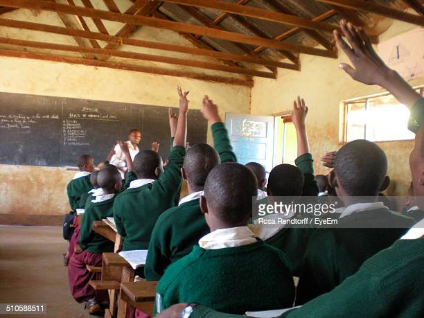 rear view of students sitting in classroom - poor africans stock pictures, royalty-free photos & images