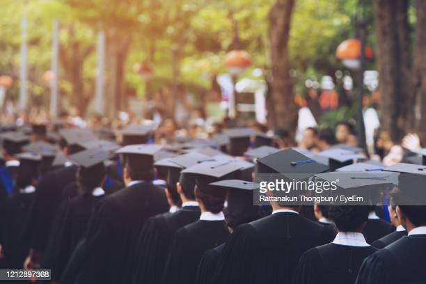 rear view of students wearing mortarboard standing outdoors - graduation crowd stock pictures, royalty-free photos & images