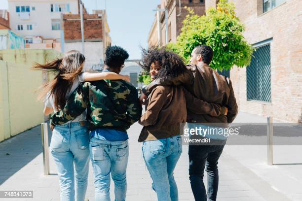 Rear view of stylish friends walking on urban street