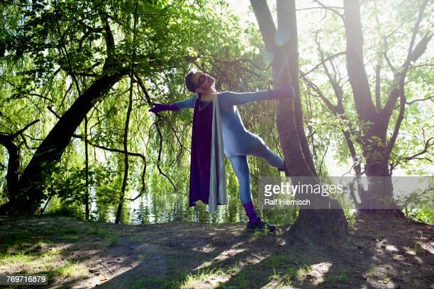 rear view of superhero standing by tree at riverbank on sunny day - flowing cape stock pictures, royalty-free photos & images