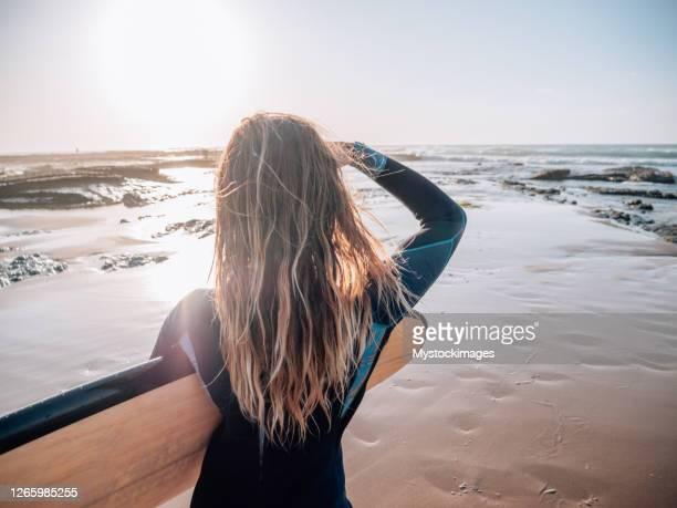 rear view of surfer woman walking on the beach at sunrise - atlantic ocean stock pictures, royalty-free photos & images