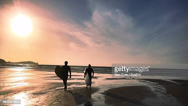 rear view of surfers carrying surfboards while walking on beach during sunset - newquay stock pictures, royalty-free photos & images