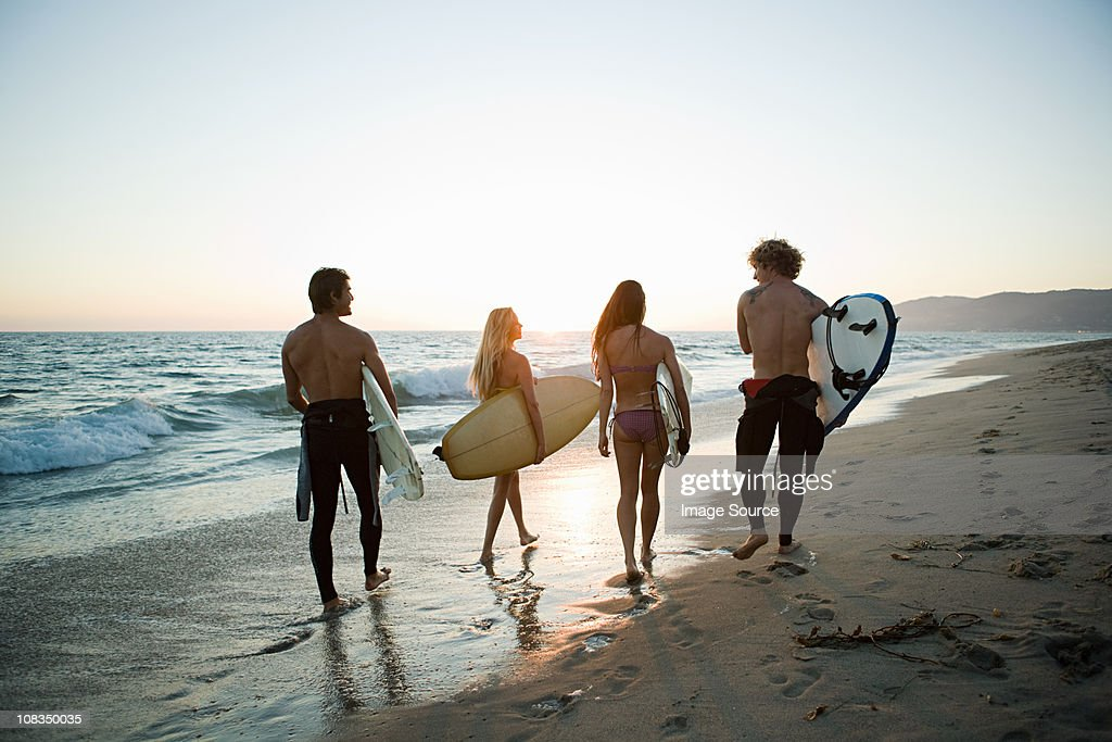 Rear view of surfers on the beach at sunset : Stock Photo